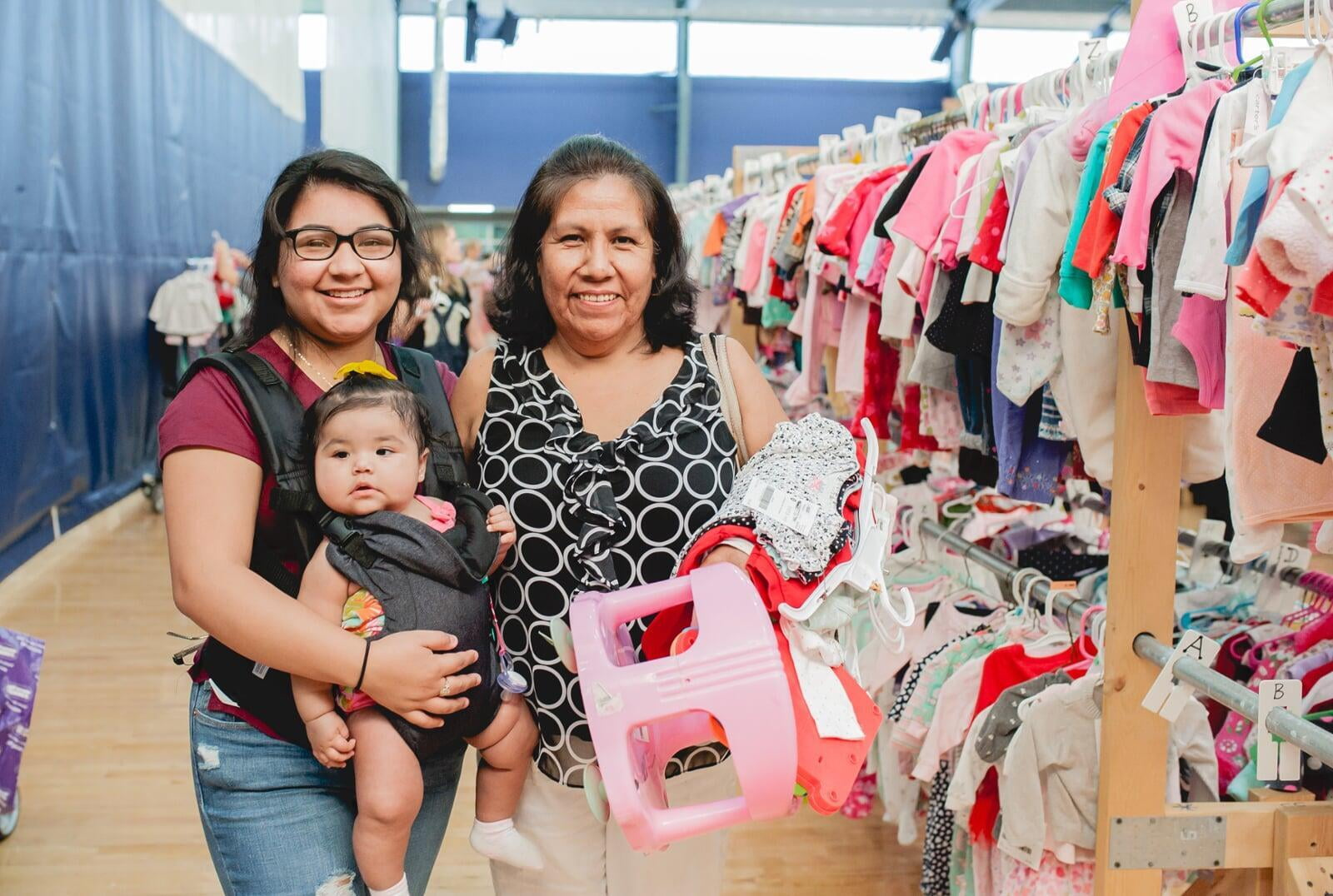 A mom, abuela and granddaughter attend a JBF sale in Dallas. Abuela is holding a babyseat.