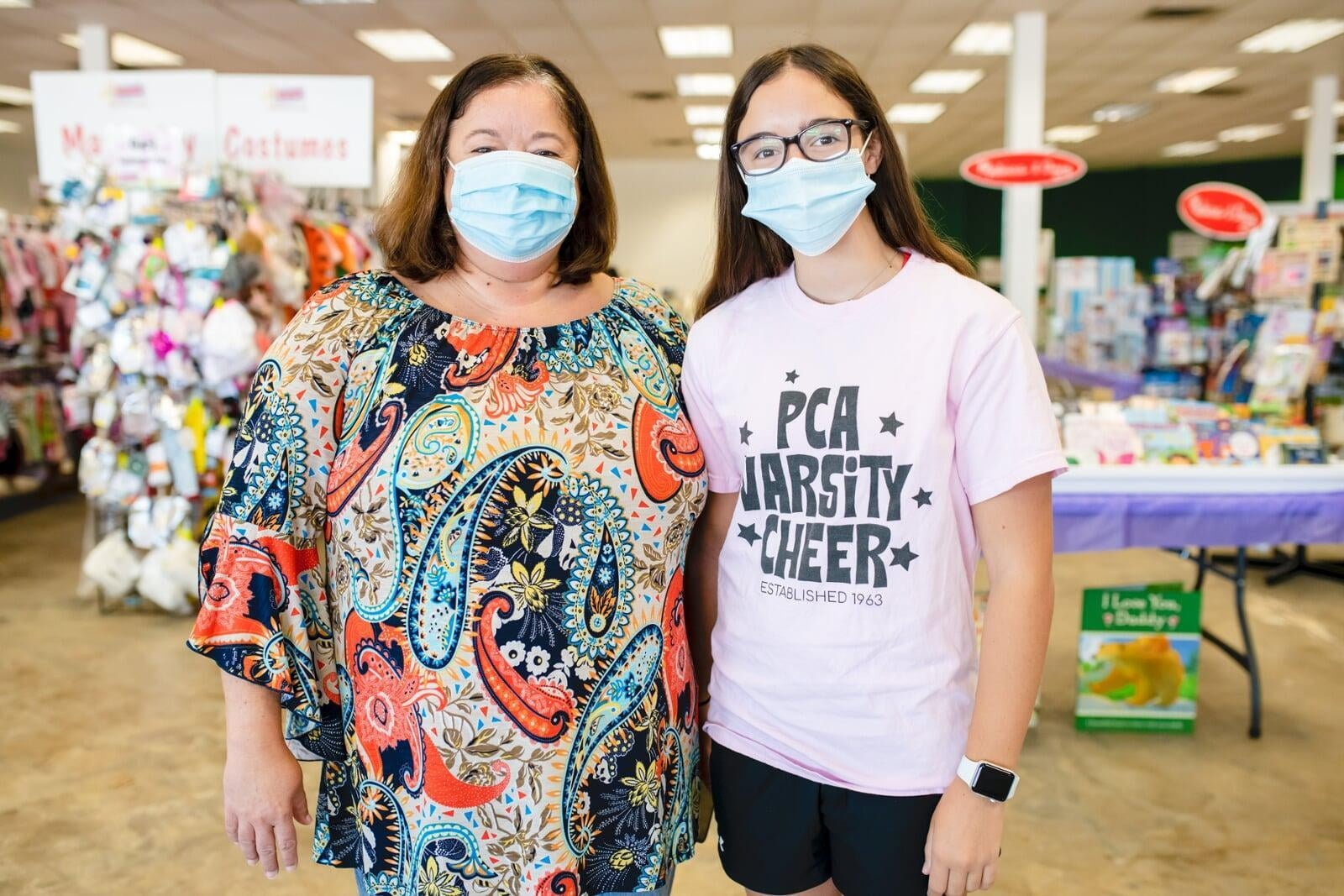 A mother and daughter stand side by side in their masks as they shop their local JBF sale.